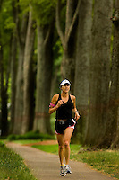 A woman runs down the sidewalk along Queens Road West in the Myers Park neighborhood in Charlotte, NC. Myers Park is one of the premier neighborhoods in North America and known for its large canopy of trees.