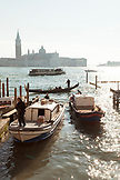 ITALY, Venice.  A view of gondola's and water taxi at the dock off Piazza San Marco. The island of San Giorgio Maggiore can be seen in the distance, dominated by the tower and dome of the Church of San Giorgio Maggiore.