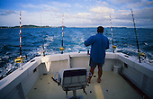 A fisherman prepares rod & tackle as a big game fishing boat heads out of the Bay of Islands. Northland, New Zealand.