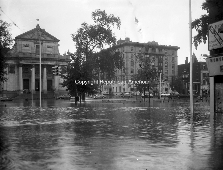 Waterbury's Green submerged by flood waters. This photo, taken from Leavenworth Street, shows Immaculate Conception Church and the Elton Hotel in the background.