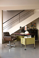 A home office with a retro desk and leather offfice chair