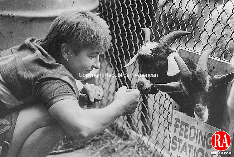 September 4, 1993 - MIDDLEBURY - A woman pets a baby goat at the feeding station at the Campership Day at Quassy Amusement Park. Republican-American Archives