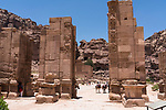 The ruins of the Triumphal Arch or Hadrian Gate built by the Romans on the Colonnade Street in the ruins of the Nabataean city of Petra in the Hashemite Kingdom of Jordan.  Petra Archeological Park is a Jordanian National Park and a UNESCO World Heritage Site.  The Qasr el-Bint or the Temple of Dushara is visible through the columns.