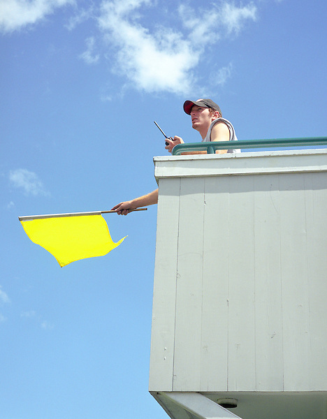 LIME ROCK, CONNECTICUT: A driving school employee waves a yellow flag during a training session to warn drivers of an accident and to reduce their speed. Lime Rock, CT, USA