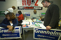 Daniel Higdon, Jr., far right, picks up road signs and political bumper stickers as he and others, including Barbara Favors, far left, wait at the Michigan Coordinated Campaign office on Woodward Ave. for the gubernatorial debates to begin on Tuesday, October 10, 2006. The office hosted a potluck dinner for a  crowd that mostly supported Granholm to watch the debate on television.&amp;#xD;photo by Danny Gawlowski.<br />