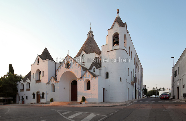 Chiesa di Sant'Antonio, or Church of St Anthony, built 1926 with trullo style conical roofs made from dry limestone with no mortar, by one of the last trullist masters, in Alberobello, Bari, Puglia, Southern Italy. The church sits on the Rione Monti hill and was built to halt the advance of Protestant proselytising. The area was first settled in the 16th century, and the feudal lord, Count Acquaviva, encouraged his peasants to build trulli to avoid taxes. Alberobello is listed as a UNESCO World Heritage Site. Picture by Manuel Cohen