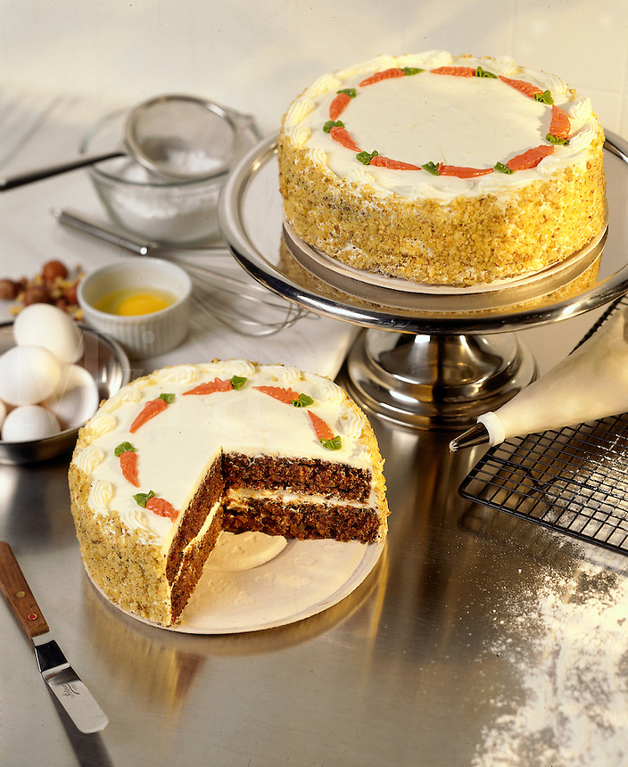 Carrot cakes on counter with baking tools.