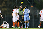 08 October 2013: Referee Hilario Grajeda (in green) shows the yellow card to North Carolina's Raby George (SWE) (33). The University of North Carolina Tar Heels hosted the Clemson University Tigers at Fetzer Field in Chapel Hill, NC in a 2013 NCAA Division I Men's Soccer match. Clemson won the game 2-1 in overtime.