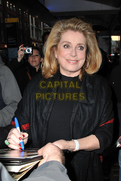 Catherine Deneuve.The 'Beloved' UK film premiere, Curzon Soho cinema, Shaftesbury Avenue, London, England..March 21st, 2012.half length top signing autographs black  .CAP/BF.©Bob Fidgeon/Capital Pictures.