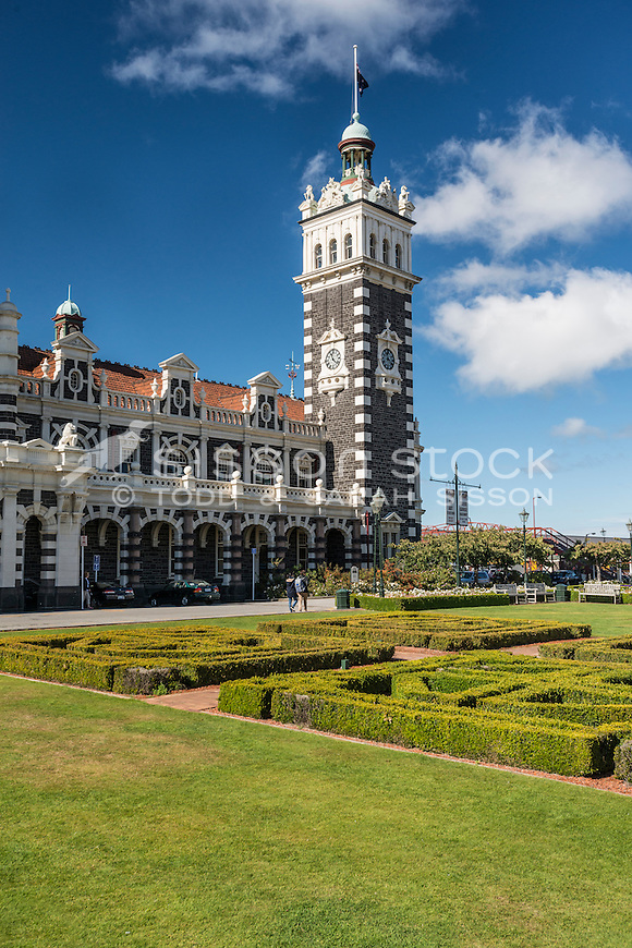 The clocktower of the iconic Dunedin Railway Station with formal shaped gardens in the foreground, Otago, South Island, New Zealand - stock photo, canvas, fine art print