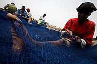 a man repairs a fishing net while awaiting for the 50th anniversary of his countries' independence in the Jamestown neighborhood in Accra, Ghana on Monday March 05 2007..