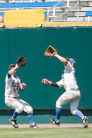 UCLA outfielders Beau Amaral and Chris Giovinazzo collide in Game 13 of the NCAA Division One Men's College World Series on June 26th, 2010 at Johnny Rosenblatt Stadium in Omaha, Nebraska.  (Photo by Andrew Woolley / Four Seam Images)
