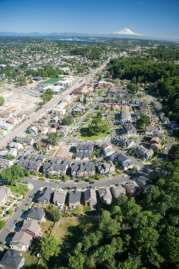 An aerial view of Rainier Vista, a mixed housing development in Seattle, WA, with nearby SoundTransit light rail and Mt. Rainier in the background.