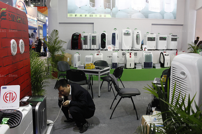 A man chats on his cellphone while squatting in front of portable air conditioners at the China Import and Export Fair in Guangzhou, Guangdong Province, China on 15 April 2010. Popularly known as the Canton Fair, the exhibition is the oldest trade fair in China, tracing its beginning to 1953. While it no longer is the only trade fair in China, it remains the biggest and most comprehensive.