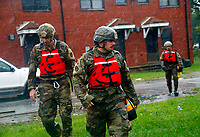 Rescue team members from the North Carolina National Guard 1/120th battalion go door-to-door as they evacuate residents in an apartment complex threatened by rising floodwaters from Hurricane Florence threatens his home in New Bern, N.C., on Friday, Sept. 14, 2018. (AP Photo/Chris Seward)