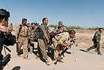 30/09/14  Iraq -- Daquq, Iraq -- Peshmerga fighters pick up a wounded comrade at the front line in Wahda village, Daquq.