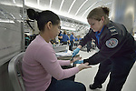 Mirna Vasquez, a refugee from El Salvador, has her hands swabbed by a TSA official in the airport in San Antonio, Texas, on December 2, 2015. Penado fled El Salvador with her daughter to escape gang-related violence. After requesting political asylum in the United States, they were held for several days by immigration officials and then released, although she wears an ankle monitors. They stayed briefly in a shelter run by the Refugee and Immigrant Center for Education and Legal Services (RAICES) and supported by a coalition of San Antonio churches, then flew to another location in the U.S. while they await final decisions on their asylum petition.