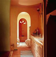 Two washbasins are set in a storage unit in the orange tadelakt bathroom