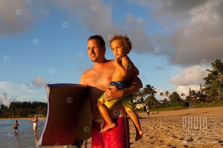 A father and son with a boogie board gaze out toward sunset at Hanalei Bay, Hanalei Beach, Kaua'i.