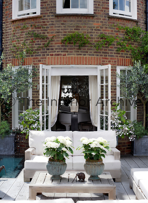 French windows open onto a sunny decked terrace furnished with comfortable outdoor sofas and a coffee table