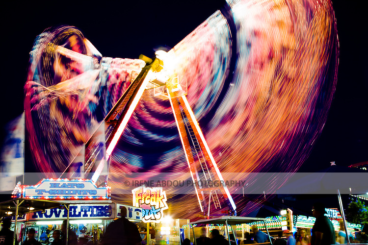 An of  ISO 100 and aperture of f/13 were just the right combination to give a shutter speed of 6.0 sec, allowing the camera to capture this Freak Out carnival ride at the Montgomery County Agricultural Fair several times along its entire length, resulting in the blur of color shown here.