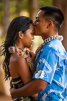 A young local man kisses his fiancée under the trees at Kailua Beach Park, Windward O'ahu.