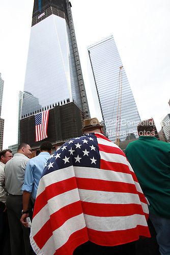 On the 10th anniversary of the September 11th attacks, Stephen Simone wears an American flag in memory of his mother, Marianne Simone, who died in 1 WTC during the 9/11 attacks. He stood at the North Memorial Pool at opening day of the September 11th Memorial at the World Trade Center site. In the background at left is the Freedom Tower in New York, New York on Sunday, September 11, 2011..Credit: Jefferson Siegel / Pool via CNP