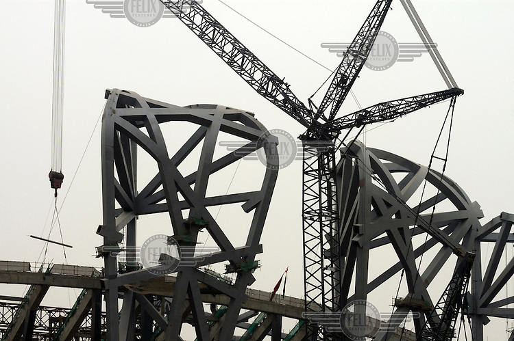 Migrant labourers at work on the construction site of the 2008 Olympic stadium. The original 'bird's nest' design by architects Herzog & de Meuron was simplified by the Chinese once the bid for the Olympic games was successful.