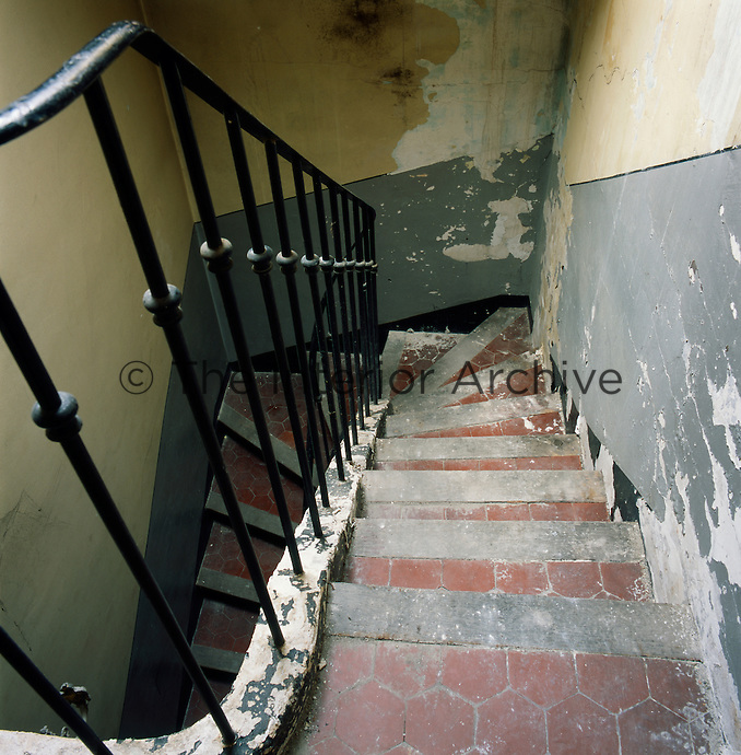 A view looking down onto a set of tiled stairs with wrought iron banister and spindles. The walls have a neglected, shabby air.