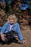 Kathi Streeter and her black laborador, Emmy, outside her home in Franktown, Colorado.  Emmy was successfully treated for osteosarcoma, a type of bone cancer, three years ago by amputating her leg and treating her with chemotherapy.  She is still alive at the age of 13.