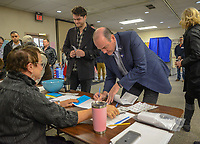 Scott Wallace signs in as the Democratic congressional candidate in the first district votes with his family Tuesday, November 06, 2018 at Buckingham Township Building in Buckingham. [WILLIAM THOMAS CAIN / PHOTOJOURNALIST]