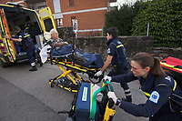 Switzerland. Canton Ticino. Massagno. A senior man lying down on an emergency medical stretcher is being transported from home. The elderly man is suffering from a blood pressure problem and needs to be brought to hospital for a medical examination. The paramedics wear blue uniforms and work for theCroce Verde Lugano. The man and the woman (R) are professional certified nurses, the third man (L) is a volunteer specifically trained in emergency rescue. The volunteer carries in his right hand a monitor which controls a set of vital functions, such as electrocardiogram, blood pressure's measurement, respiratory rate and pulse oximetry (oxygen saturation), and on his left hand an intravenous infusion with saline solution.TheCroce Verde Lugano is a private organization which ensure health safety by addressing different emergencies services and rescue services. Volunteering is generally considered an altruistic activity where an individual provides services for no financial or social gain to benefit another person, group or organization. Volunteering is also renowned for skill development and is often intended to promote goodness or to improve human quality of life. Massagno is a quarter of the city of Lugano. 14.01.2018 © 2018 Didier Ruef
