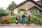 """Andrew and Patricia Nimelman cosult with Donna Smith (otherwise known as """"Your Backyard Farmer) at their home in NE Portland, OR.  Also present is their son, Lucas."""