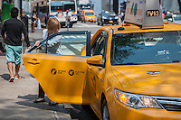 A passenger exits a taxi on Fifth Avenue in New York on Thursday, September 3, 2015. Because of the rise in Uber and other apps taxi medallions have decreased in worth to about $900,000 with loan delinquencies on the rise. The Melrose Credit Union has $168 million in delinquencies as of May 2015 while in January 2014 it had only $32,000. In the next six months Melrose has $212 million in maturing loans which many owners will be unable to pay.   (© Richard B. Levine)