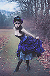 gothic young woman in the woods curtsies, wearing a fancy purple gown and a mysterious blindfold over her eyes