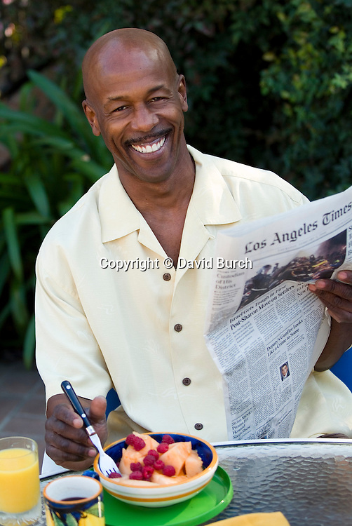 Mature man holding newspaper, smiling, portrait