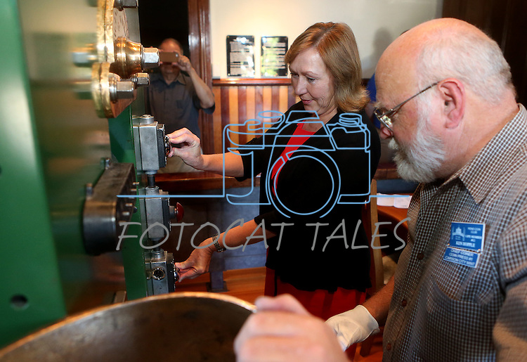 Coiner Ken Hopple watches Pam Robinson mint a medallion of the fourth and final in a commemorative Sesquicentennial series at the Nevada State Museum, in Carson City, Nev., on Wednesday, Sept. 3, 2014. <br /> Photo by Cathleen Allison