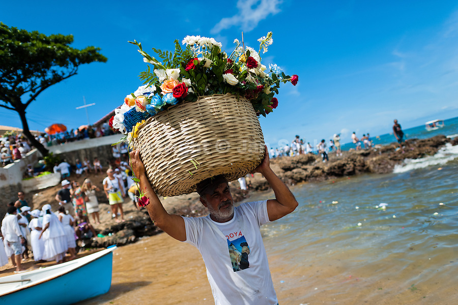 A Candomblé follower caries a basket of flowers during the festival of Yemanjá, the goddess of the sea, in Salvador, Bahia, Brazil, 2 February 2012. Yemanjá, originally from the ancient Yoruba mythology, is one of the most popular ?orixás?, the deities from the Afro-Brazilian religion of Candomblé. Every year on February 2nd, thousands of Yemanjá devotees participate in a colorful celebration in her honor. Faithful, usually dressed in the traditional white, gather on the beach at dawn to leave offerings for their goddess. Gifts for Yemanjá include flowers, perfumes or jewelry. Dancing in the circle and singing ancestral Yoruba prayers, sometimes the followers enter into a trance and become possessed by the spirits. Although Yemanjá is widely worshipped throughout Latin America, including south of Brazil, Uruguay, Cuba or Haiti, the most popular cult is maintained in Bahia, Brazil.