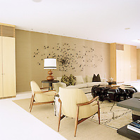 The living room is furnished with a pair of 1940s French armchairs and a large butterfly installation by Paul Villinski dominates the wall above the sofa
