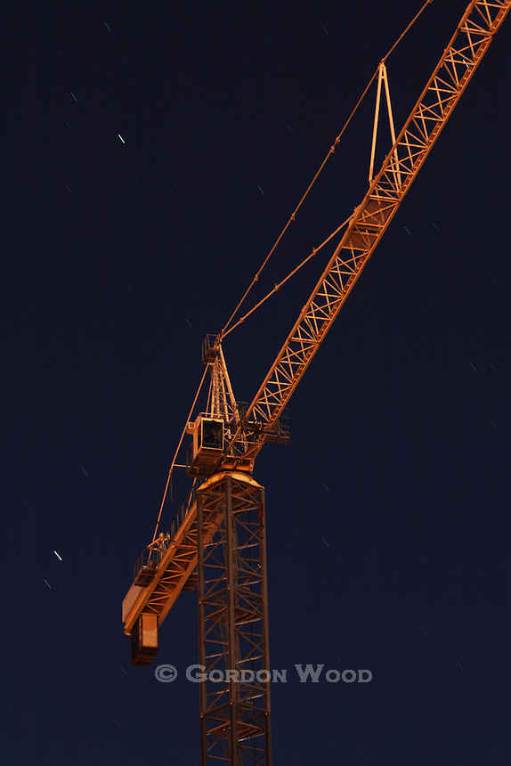 Construction Crane at Night Illuminated by Street Lights with Star Trails in the Sky