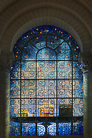 Large stained glass window of the Treasury, with form of a cross in interlacing lead patterns, in blue glass, made by Ateliers Loire, Chartres, seen from the transept, in Angouleme Cathedral, or the Cathedrale Saint-Pierre d'Angouleme, Angouleme, Charente, France. The 12th century Romanesque cathedral was largely reworked by Paul Abadie in 1852-75. In 2008, Jean-Michel Othoniel was commissioned by DRAC Aquitaine - Limousin - Poitou-Charentes to display the Treasure of the Cathedral in some of its rooms, which opened to the public on 30th September 2016. Picture by Manuel Cohen. L'autorisation de reproduire cette oeuvre doit etre demandee aupres de l'ADAGP/Permission to reproduce this work of art must be obtained from DACS.