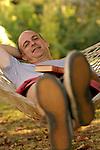 Mid adult man lying on hammock, portrait