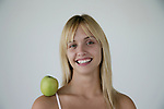 Portrait of a young woman with a granny smith apple on her shoulder