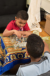 5 year old boy playing chess game with 10 year old brother, listening to his advice