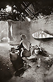 ERITREA, Galallo, a woman makes injera bread at a small roadside restaurant called Ali's (B&W)