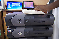 A technician installs software on a stack of old Dell desktop  computers. Accra New Town.