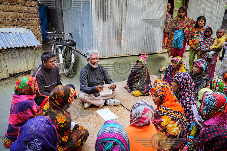 Rafiqul Alam, an anti-povery activist who runs the NGO Dwip Unnayan Songstha (DUS), meeting with residents relocated from Charaktin village after storms destroyed their homes.