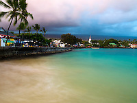 A camera's slow shutter speed at sunset softens the trees and water in this perspective of historic Kona Town (or Kailua-Kona Town), Big Island.