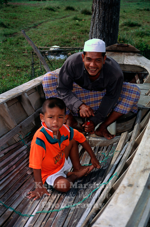 Local Muslim father and son repairing their boat. AoNang (Krabi province) - Southern Thailand.