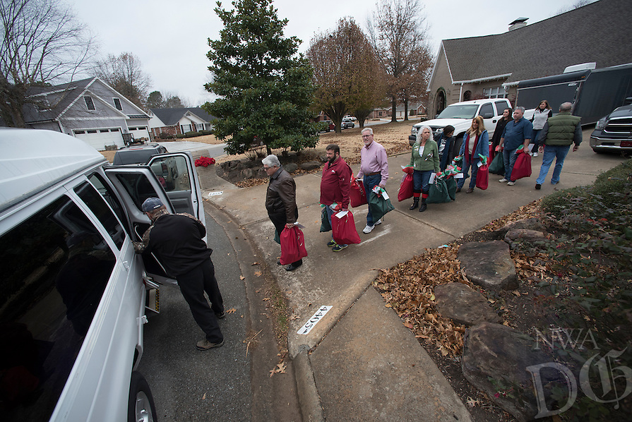 NWA Democrat-Gazette/J.T. WAMPLER Around 15 volunteers line up help Jim Batlle ((CQ)) (left) of Farmington load food bags Sunday Dec. 11, 2016 for the Farmington Senior Center. The Chase Foundation has been giving holiday food packages to home-bound seniors for seven years through donations to senior centers in Farmington, Prairie Grove, Greenland, Elkins and West Fork. After Sunday's delivery the foundation will have served 931 seniors since 2009. Each senior receives nearly 70 pounds of food for the holiday season. Extra food is destined to the Peace at Home Family Shelter, Seven Hills Homeless Center and Northwest Arkansas Women's Shelter.